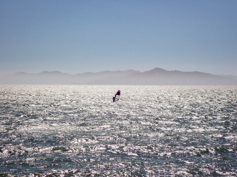Lone windsurfer sailing across San Francisco bay under blue skis