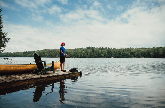Teen boy fishing from a dock on a calm lake in the summer.