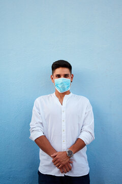 Young latin man with mask on blue background