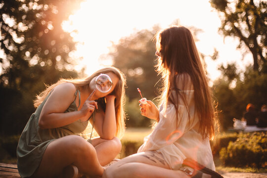 Happy girlfriends playing with bubbles in park during summer