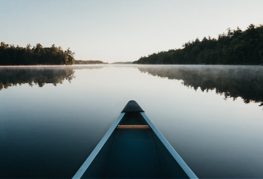 Bow of a canoe in the morning on a misty lake in Ontario, Canada.