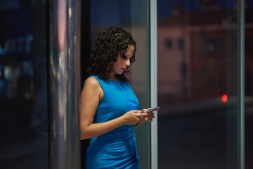 Night portrait in the city of a young woman with her smart phone. Fotomurales