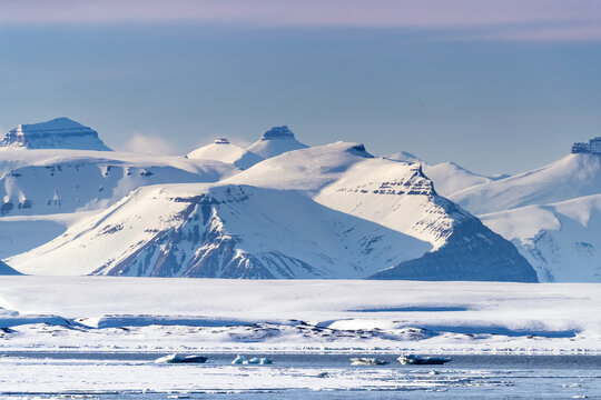 The Tre Kroner, or Three Kings mountain range, Svalbard. Landscape of pristine snow covered peaks, fast ice and icebergs on the Nordfjorden coastline of the arctic ocean.