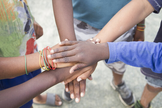 anonymous group of different race children putting hands together in an outdoor natural environment concept of togetherness