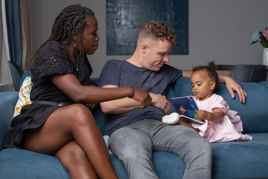 Multiracial family sitting with their daughter on a couch