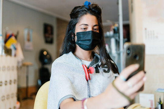 Woman in the hairdresser's with a mask, look at the smart phone.