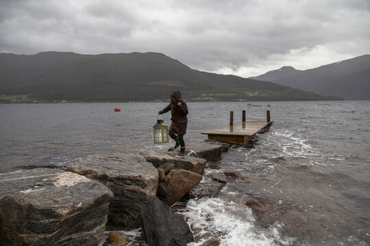 A woman carrying a lantern along a stone jetty next to a fjord