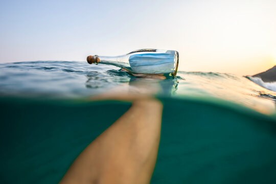 Holding a Covid-19 surgical face mask inside a glass bottle in the sea
