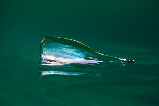 Covid-19 face mask inside a glass bottle floating in the ocean