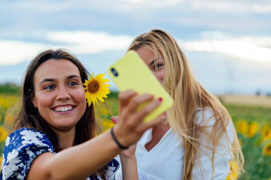 A couple of attractive young women one blonde and the other brunette posing in their designer dresses in a field of sunflowers using their smartphone