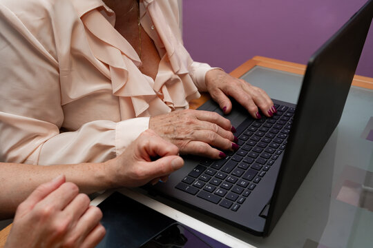 close up of elderly woman typing on a laptop