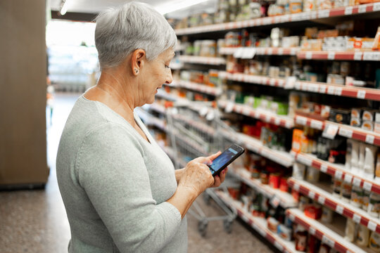 Caucasian elderly woman with white hair  shopping in supermarket