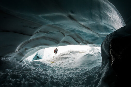 Mountaineer and explorer rappels into glacial ice cave to have a look.