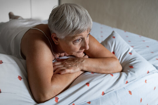 Caucasian elderly woman with white hair in the bed