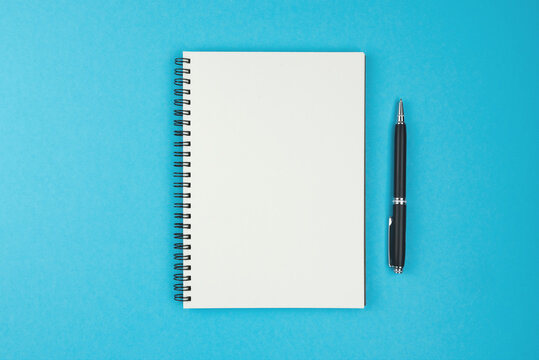 directly above view of blank spiral bound notebook and ballpoint pen on blue background