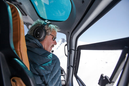 Helicopter pilot looks for a place to land in snow covered mounatins.