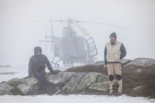 Helicopter pilot and passenger wait on mountain for weather to clear.