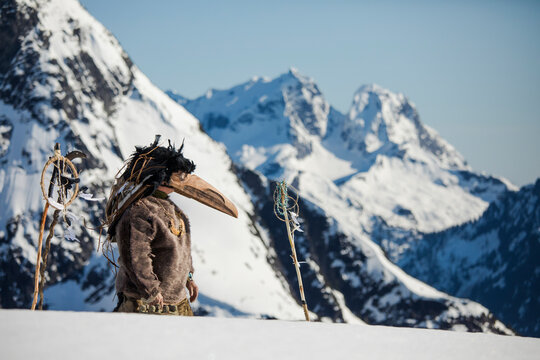 First Nations person dressed in Ravens mask preforms a ceremony.