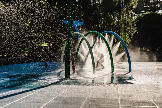 Silhouette of child running through water at park