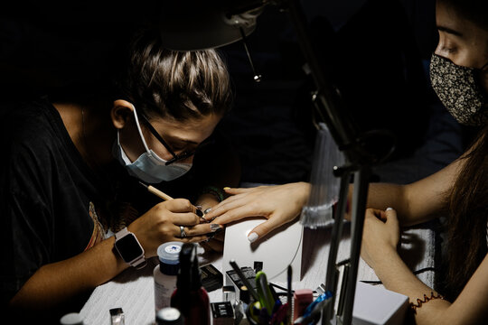 Female stylist in mask making manicure to woman during COVID epidemic