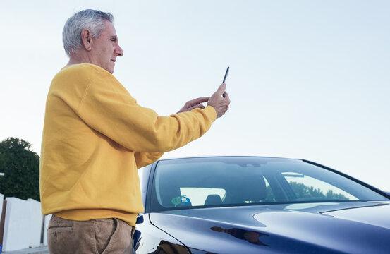 Elderly traveler using smartphone near car