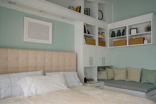 Clean modern bedroom with display shelves and reading nook bench