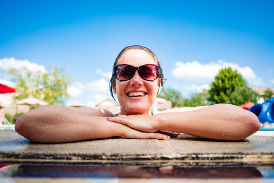 smiling woman in a pool on a hot summer day
