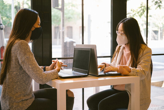 Two friends, one Caucasian and one Asian, are sitting at a restaurant table to work on their computer wearing a covid mask