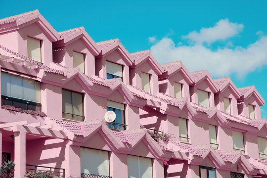 Row of houses in a bizarre pink color in a residential neighborhood.