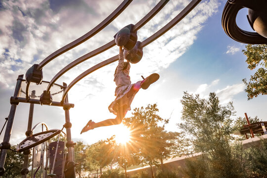 young girl swings her legs on a moving monkey bar at a playground