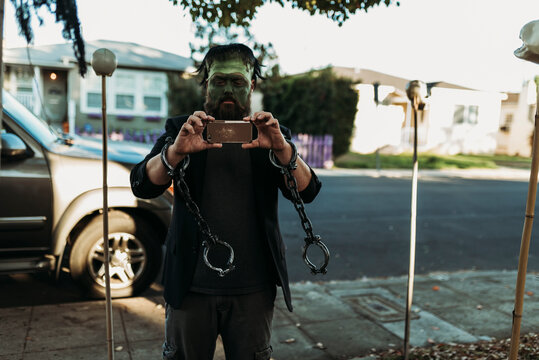 Father dressed as Frankenstein holding phone during Trick-or-Treat