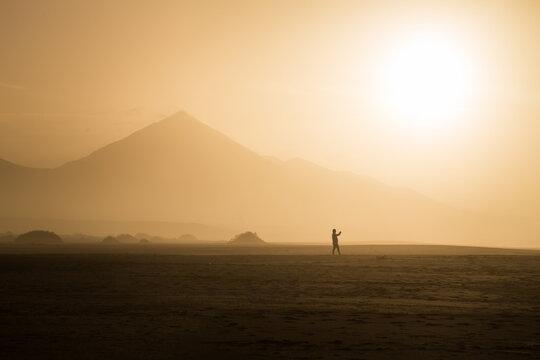 Silhouette of man walking on Cofete beach at sundown in Fuerteventura, Canary Islands, Spain.