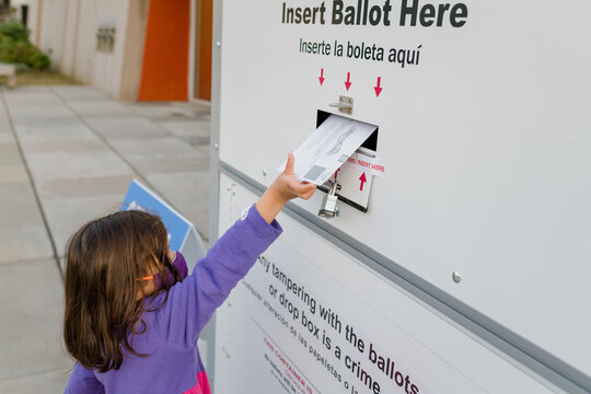 Little girl placing ballot in a drop box for absentee voting