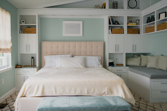 bright bedroom interior with built in bookshelves and bench