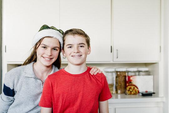 Portrait smiling siblings teenagers by kitchen gabinet