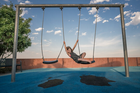 young girl plays on a swing holding another swing at a playground