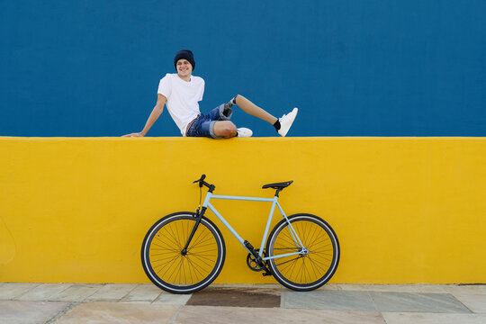 Young male with disability sitting near bike