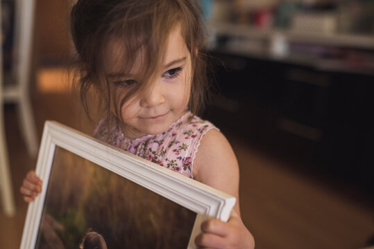 Sweet brown-eyed 4 yr old girl with wispy hair holding framed picture