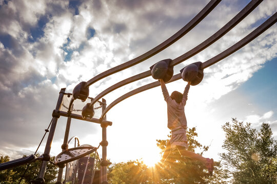 young girl swings from a moving monkey bar at a playground