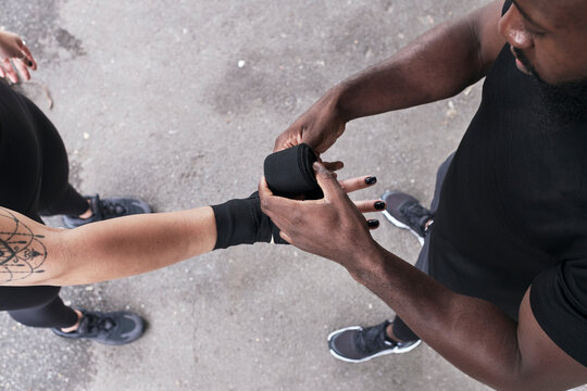 Coach Wrapping Woman's Hands Before Practicing Boxing.