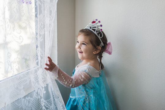 Smiling girl in princess costume and tiara touching white lace curtain