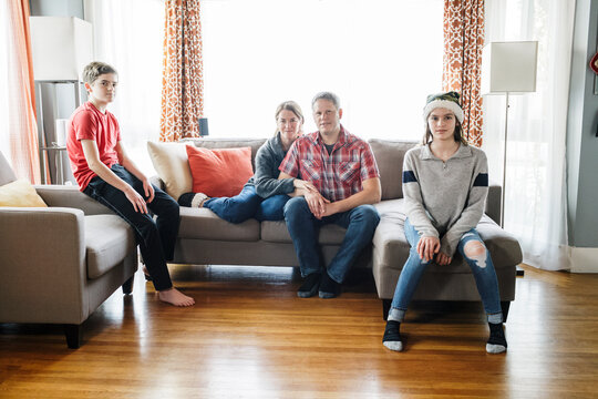 Editorial Portrait of family with teenagers on sofa at living room at home