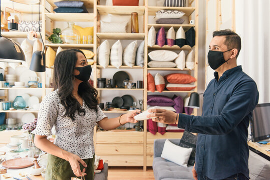 Customer and business owner smiling at each other making purchase