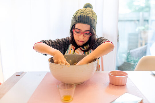 boy with green hat and red reading glasses kneading bread dough at home table