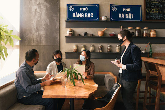 Masked up friends and waiter taking order at Vietnamese restaurant