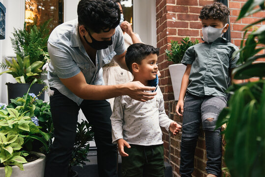 Father helping son adjust mask before heading out to play from home