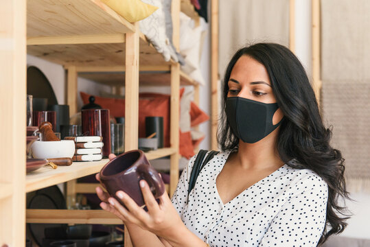 Woman wearing mask and browsing products in artisan home decor store