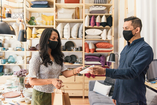 Masked shopper and store owner making purchase with credit card