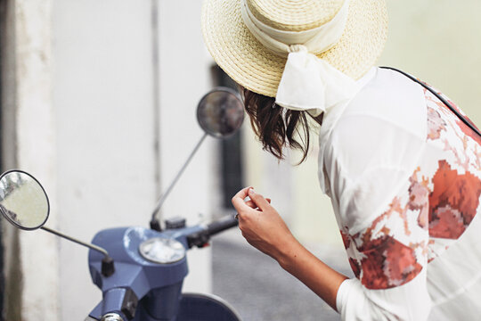 Woman in a straw hat looking at a bike mirror and fixing her makeup