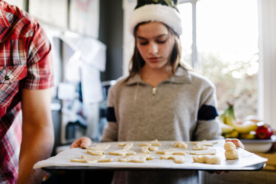 Girl wearing santa hat holding tray with sugar cookies dough over Parchment paper.